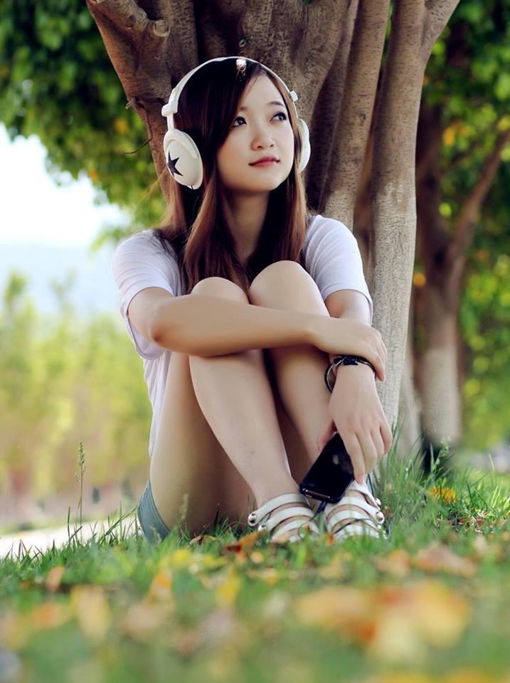 Em xinh ngồi nghe nhạc dưới gốc cây