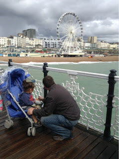 Toddler in buggy and Hubbie watching Brighton Wheel