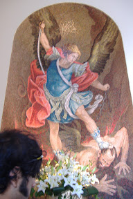 One guy with wings (an angel? Devil?) getting beat down by another guy with wings and a sword.
