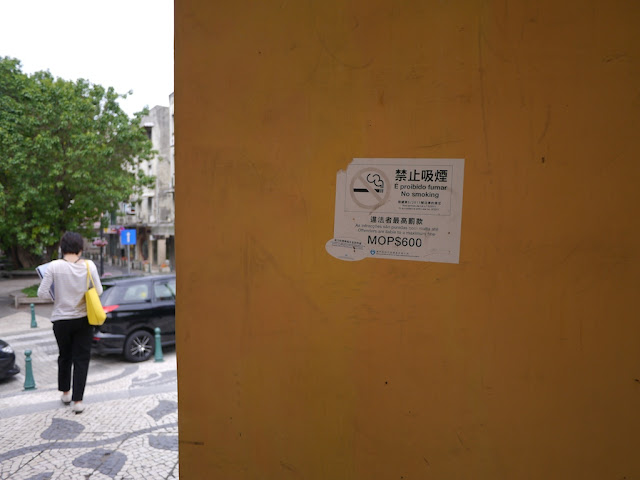 a no smoking sign on an outdoor wall in Macau