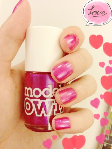 A picture of someone holding a pink Model's Own nail varnish bottle showing the colour on the nails