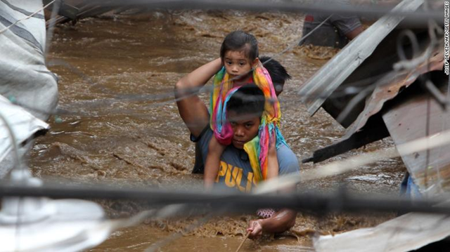 A police officer carries a young girl on a flooded street in Cagayan de Oro on Friday, 22 December 2017. Photo: Josep Deveza / AFP / Getty Images