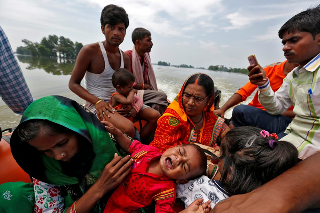 A family is rescued from a flooded village in the eastern state of Bihar, India on 23 August 2017. Photo: Cathal McNaughton / Reuters