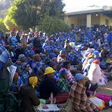 Women sit apart from men.  Blue shawls indicate these women have been initiated