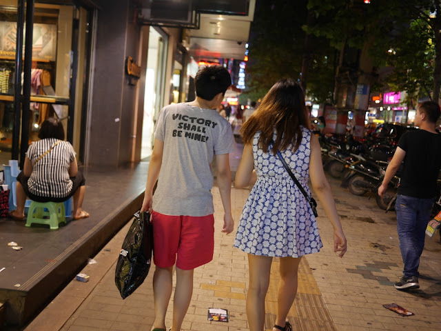 "young man wearing a shirt with ""VICTORY SHALL BE MINE!"" on the back walking with a young woman"