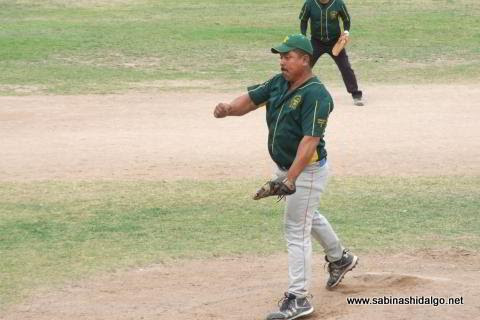 Candelario García lanzando por Amigos en el softbol dominical.