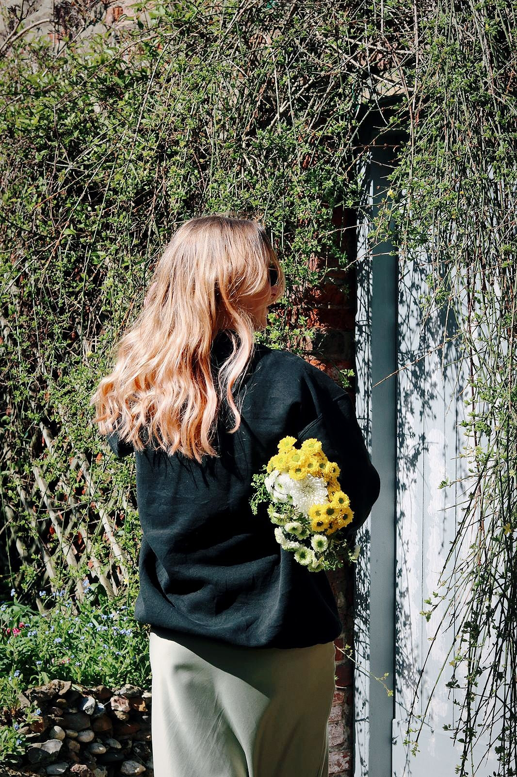 Amy is in an overgrown garden, facing away from the camera holding a bunch of flowers under one arm