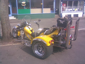 yellow large cc trike parked infront of shops