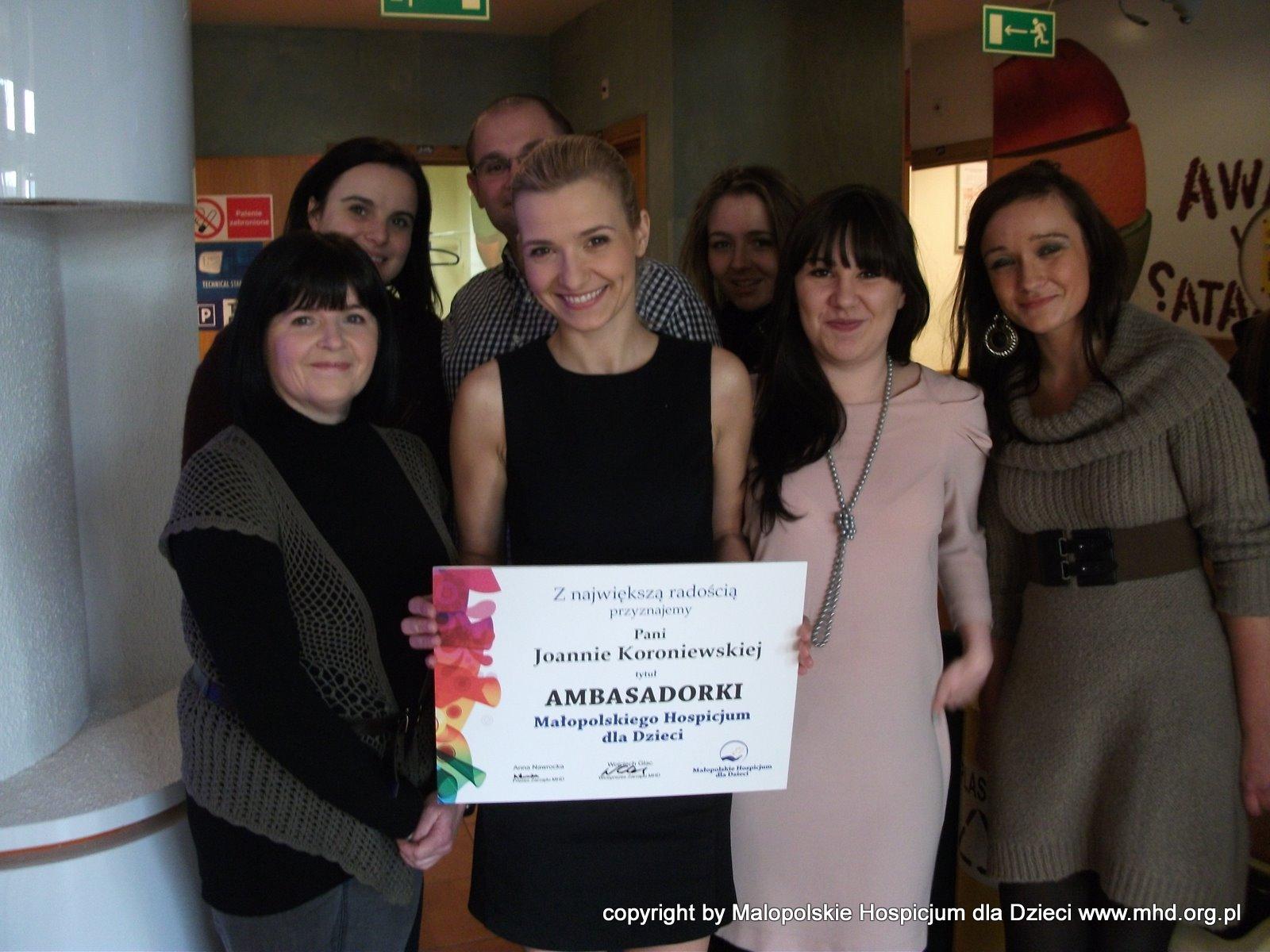 Joanna Koroniewska 10 lutego 2012 roku została Ambasadorką Małopolskiego Hospicjum dla Dzieci.  Na zdjęciach wspólnie z Panią Krystyną Jastrzębską - mamą Naszej Ani, podczas nagrania spotu TV kampanii pomozbudowac.pl
