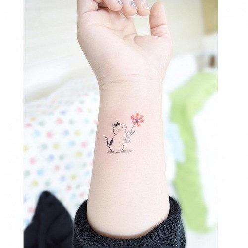 este_doce_de_gato_segurando_uma_flor_de_tatuagem