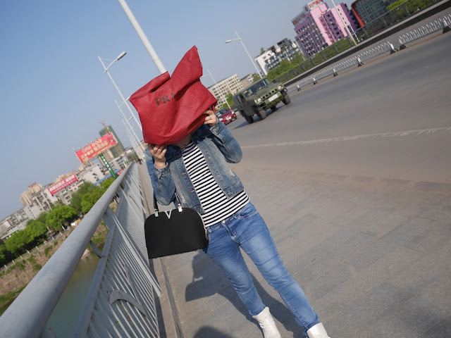 young woman walking while holding a red bag over her head