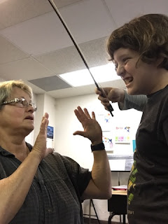 Student using a violin bow to hit a teacher