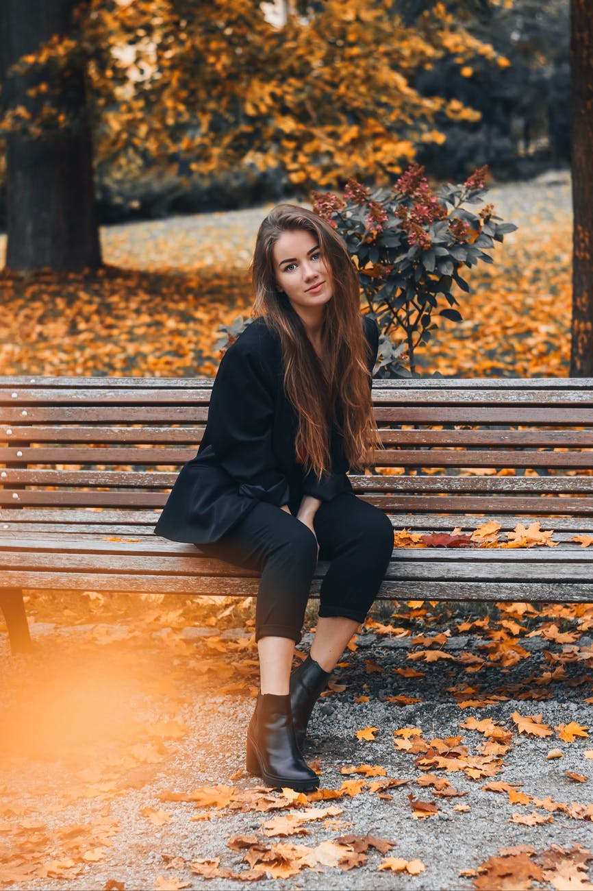 elegant lady wearing a suit sitting on a park bench in Fall