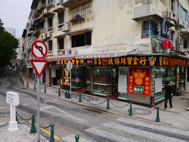 a street scene in Macau with a variety of signs