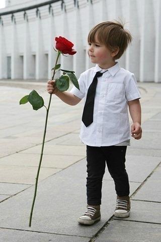 Малыш держит красивую длинную розу
