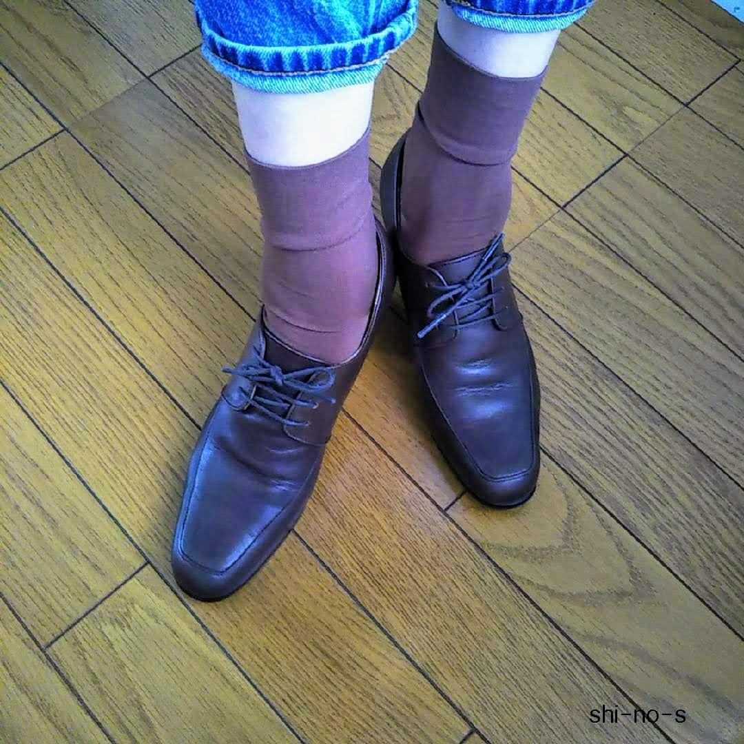 茶色の紐靴と茶色のナイロンソックスを、履いている足元のアップ