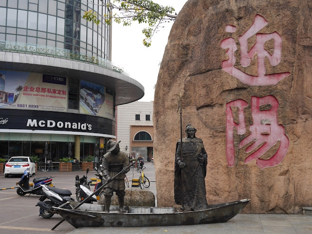 statues of two men on a boat in front of large Chinese characters and a McDonald's