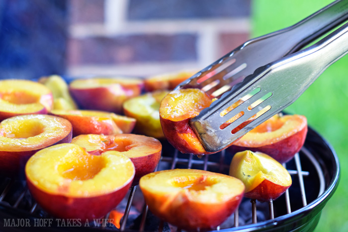 Use tongs to grill peaches on a charcoal grill