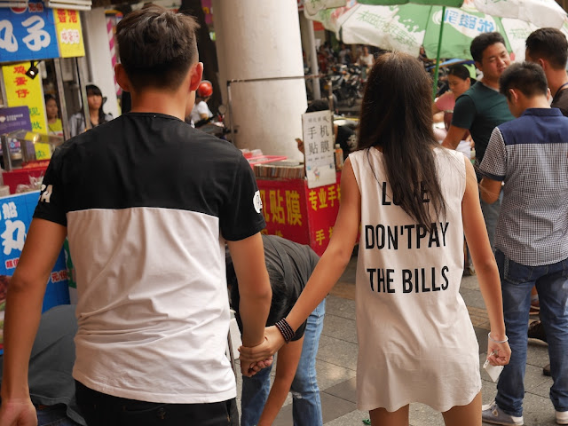 "female wearing a shirt with ""LOVE DON'T PAY THE BILLS"""