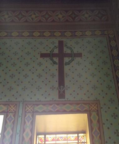 A figura representa os instrumentos prefigurativos dos sofrimentos da paixão e morte do Salvador: a Cruz, coroa de espinhos e os cravos.
