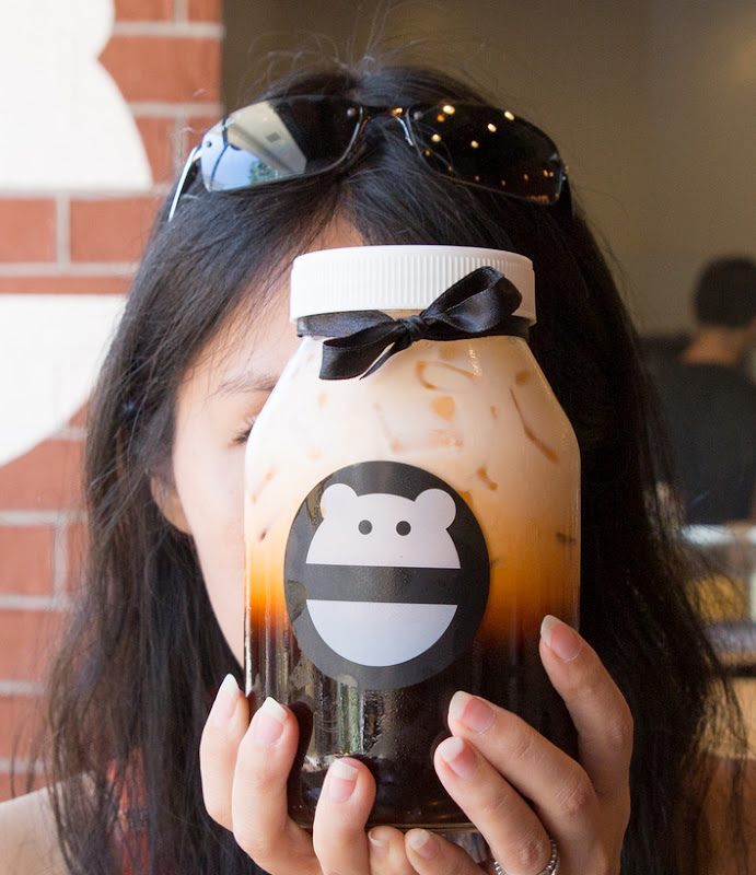 photo of a girl holding the jar of Thai Tea in front of her face