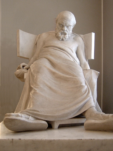 This is a statue of Socrates slumped in a chair, head down and eyes closed after he succumbed by drinking the poisoned hemlock.