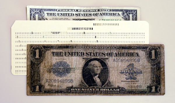 The dimensions of IBM punched cards were based on the large-sized notes used for US currency until 1929. The punched card and the 1923 $1 silver certificate in the foreground are roughly the same size, considerably larger than the modern dollar at the back.