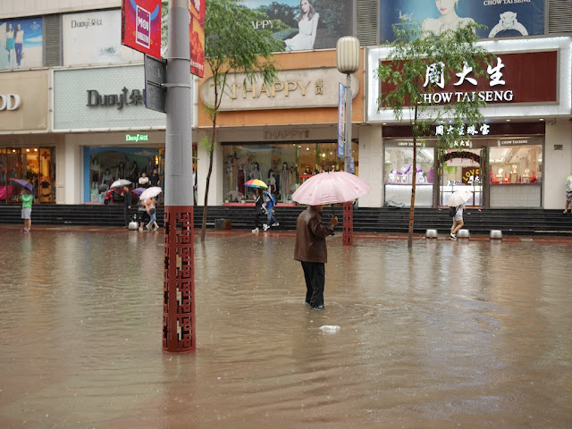 man standing in a flooded street in Taiyuan, China