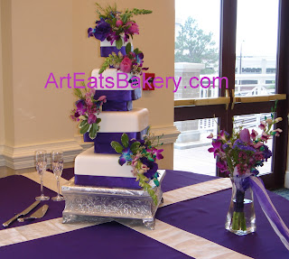 Unique four tier custom square fondant wedding cake design with Purple ribbons, separators and flowers