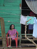 Date: January 2004  Location: Roatan Island, Honduras  Old lady sitting outside her daughters house.  The daughter is inside the house.  Her mother (?) is sitting outside, obviously not in a ggod state.  There is a barbed wire fence in front of her.  Vivid colours.