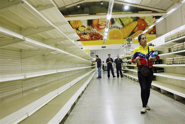 A woman walks past empty shelves at a supermarket in San Cristobal, Venezuela, on 16 January 2018. Photo: Carlos Eduardo Ramirez / Reuters