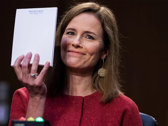 Amy Coney Barrett holds up an empty notepad and flashes a shit-eating smirk. (TOM WILLIAMS / CQ-ROLL CALL, INC VIA GETTY IMAGES)