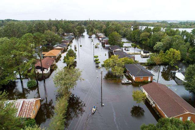 Two people in a canoe paddle through a street that was flooded by Hurricane Florence on 16 September 2018, north of New Bern, North Carolina. Photo: Jim Lo Scalzo / EPA-EFE / REX / Shutterstock