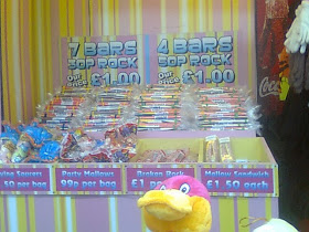 Cuddly toy encroaching humourously into holiday rock candy display