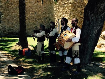 4 musikanter i en park foran bymuren.