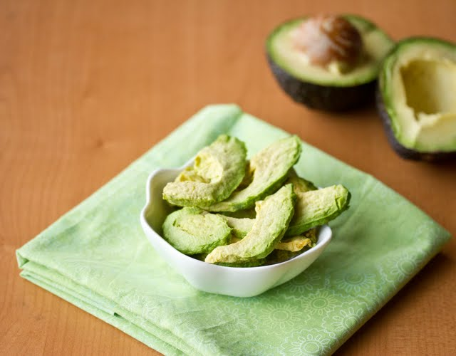 avocado chips in a white bowl with a green napkin and a sliced avocado in the background