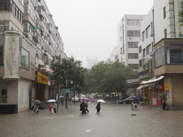 people crossing a flooded street in Taiyuan, China