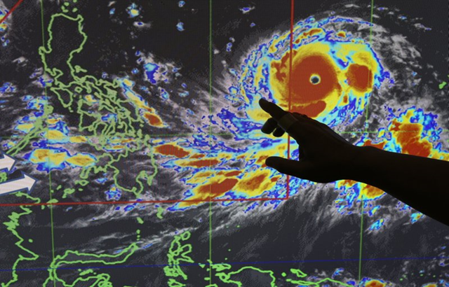"""Filipino forecaster Meno Mendoza illustrates the path of Typhoon Mangkhut, locally named """"Typhoon Ompong"""" as it approaches the Philippines with sustained winds of 205 kilometers per hour (127 miles per hour) and gusts of up to 255 kph (158 mph), at the Philippine Atmospheric, Geophysical and Astronomical Services Administration in metropolitan Manila, Philippines on Wednesday, 12 September 2018. Philippine officials say they plan to evacuate thousands of villagers, shut down schools and offices and scramble to harvest rice and corn as the most powerful typhoon so far this year menacingly roars toward the country's north. Photo: Aaron Favila / AP Photo"""