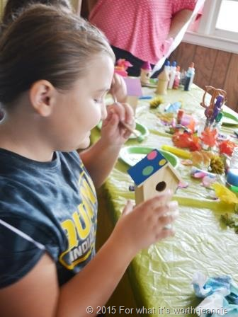child painting bird house