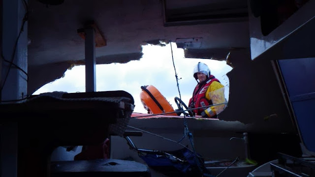 An ILB crew member looks through the gash on the side of the stricken catamaran - 24 December 2013.  Photo credit: RNLI/Poole