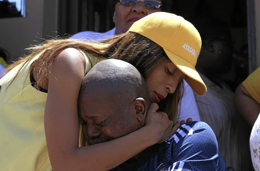 Maskandi singer Ndlovukazi hugs a tearful Sam Meyiwa, the father of murdered footballer Senzo Meyiwa, after she donated R6000's worth of groceries to the family in Umlazi, outside Durban.