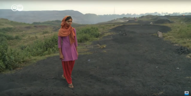 Screenshot from a Deutsche Welle documentary, 'The hellish coal fields of Jharia', showing Savitri Mahto, a young coal scavenger at the coal mine in the Jharia neighborhood of the Indian city of Dhanbad. There the 17-year-old toils away for hours every day in order to support her family. The toxic fumes are destroying Savitri's health, but she cannot afford to see a doctor. Photo: DW English