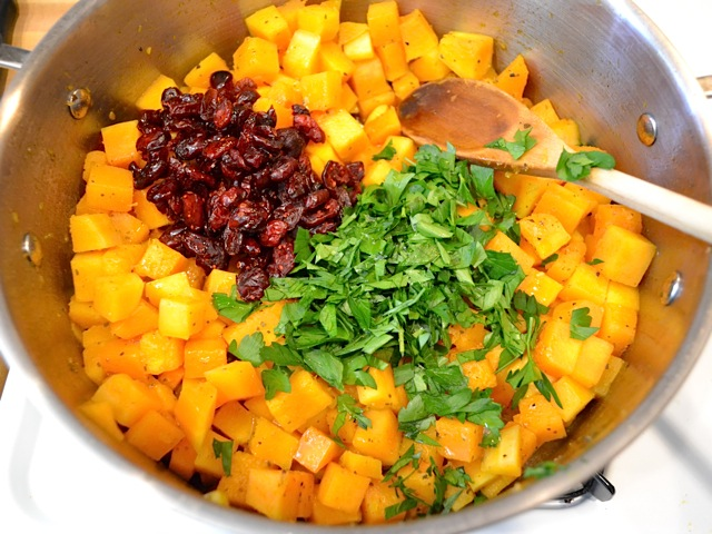 cranberries and parsley added to squash in pot