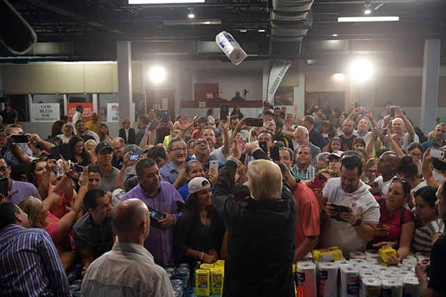 President Donald Trump throws a paper towel roll into the crowd as he visits the Cavalry Chapel in Guaynabo, Puerto Rico, on 3 October 2017. To many Puerto Rican residents, that image — Trump's arms arched as if shooting a three-pointer — illustrated the president's cavalier attitude towards the island. Photo: Mandel Ngan / AFP / Getty Images