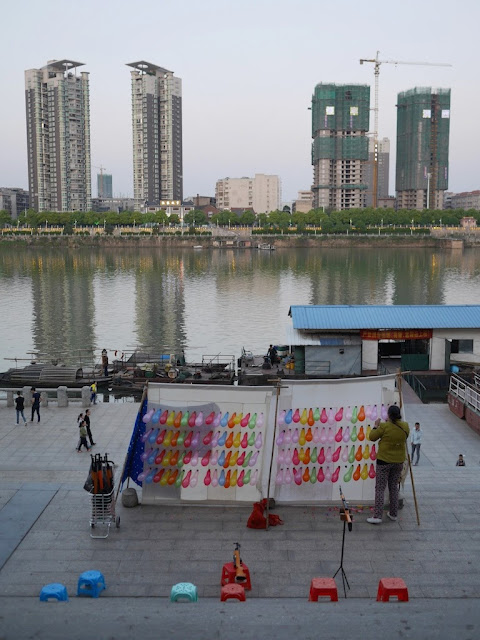 woman setting up balloons to shoot with tall buildings under construction in the background