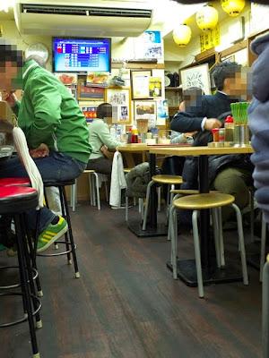 店内のテーブル席、テレビでは競馬中継が流れてる