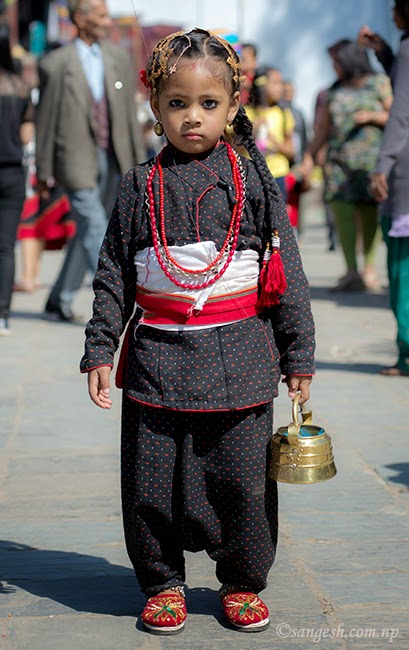 A young child dressed in the traditional newari dress