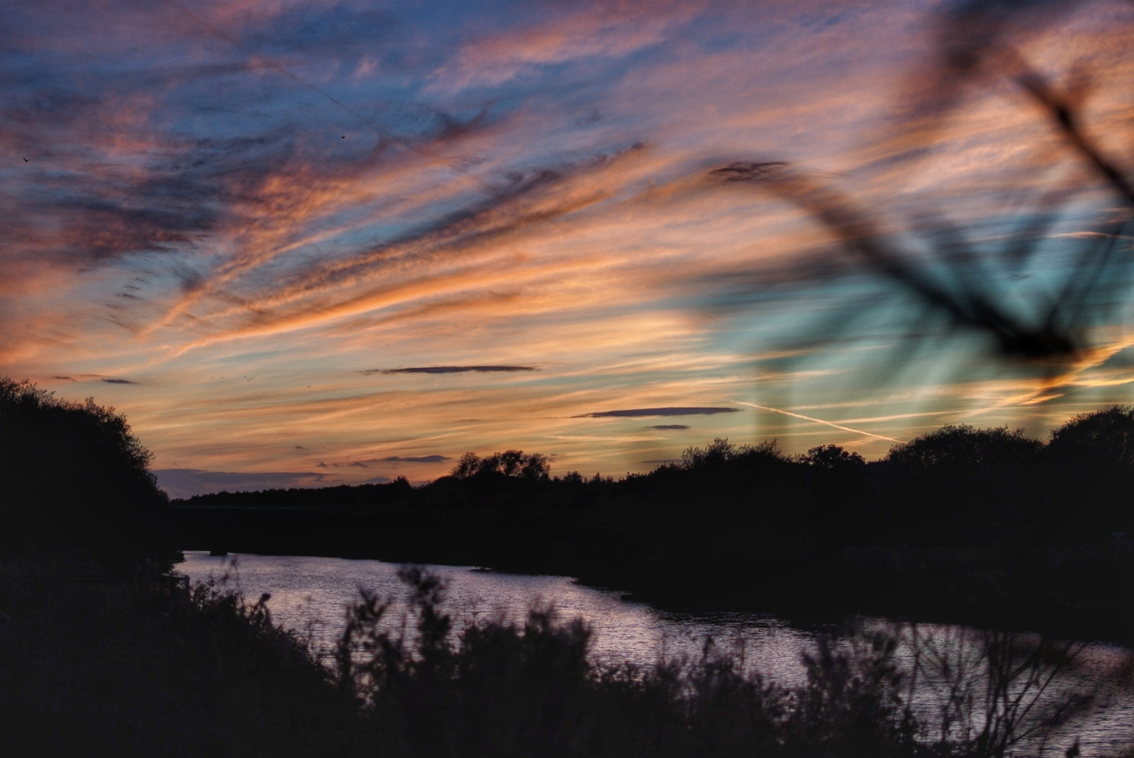 Landscape of a river with banks either side, above is a beautiful sunset; the sky is a mixture of blues, oranges, pinks and purples.