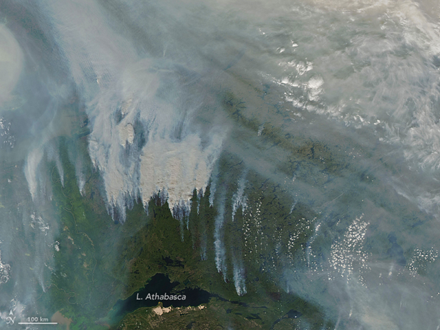 Smoke over Canada's Northwest Territories and Yukon and Nunavut provinces, captured by the Aqua satellite on 14 August 2017. This smoke joined with another smoke band from fires in British Columbia. The fires in BC were so intense that they produced several pryocumulus clouds, lofting smoke up to 13 kilometers (8 miles) into the atmosphere. Photo: Joshua Stevens / NASA Earth Observatory