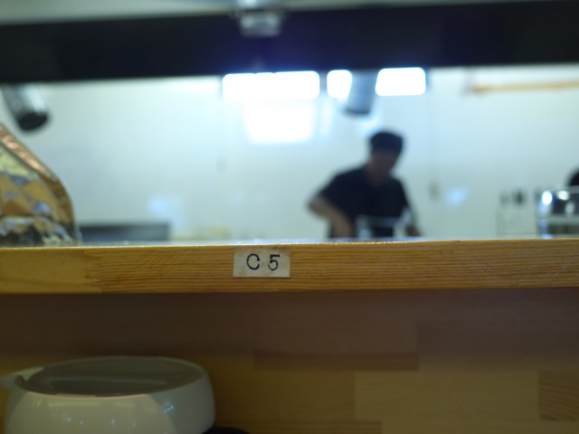 カウンター席の番号。カウンター越しに店員さんが鍋を振られてる
